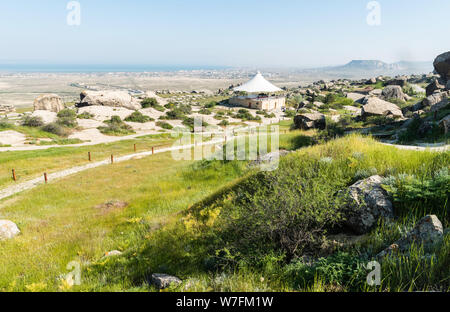 Gobustan, Azerbaijan - May 1, 2019. Landscape in Gobustan national park, with pathways, pavilion, people and Gobustan settlement in the distance. - Stock Photo