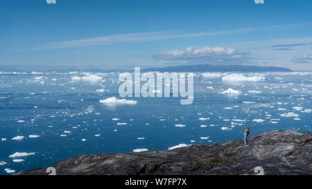 A tourist looking at the Disko Bay with ice blocks coming from the Ilulissat ice fjord, near Ilulissat in western Greenland. - Stock Photo