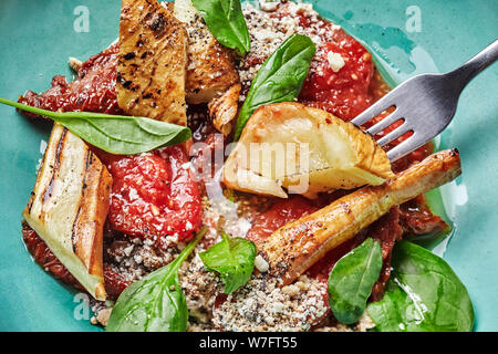 Meat with potatoes and vegetables served on a wooden table. - Stock Photo
