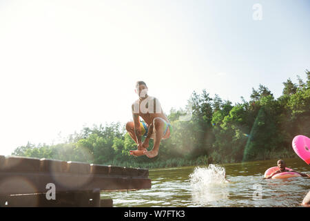 Happy group of friends having fun while laughting and swimming in river. Joyful male models jumping, splashing water at riverside in sunny day. Summertime, friendship, resort, weekend concept. - Stock Photo
