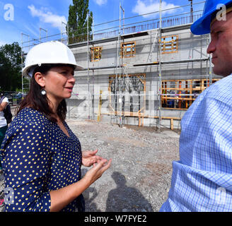 Erfurt, Germany. 06th Aug, 2019. Anja Siegesmund (Bündnis90/Die Grünen), Environment Minister of Thuringia, speaks with a man at the construction site for a hydropower plant. The hydroelectric power station is a station of the summer tour of Siegesmund. The tour leads over 9 days and 24 stations along the green and the blue band through Thuringia. At the edge of the grounds of the Federal Garden Show 2021 in Erfurt, a new hydroelectric power station is being built to generate energy and irrigate meadows and fields. Credit: Martin Schutt/dpa-Zentralbild/dpa/Alamy Live News - Stock Photo