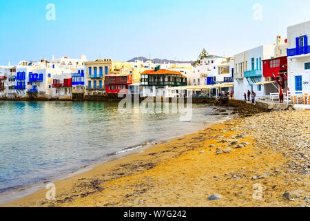 Mykonos, Greece - April 23, 2019: People, typical greek white houses in Little Venice part of Myconos town - Stock Photo
