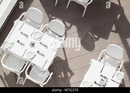 White tables and chairs stand at an empty outdoor terrace, top view - Stock Photo