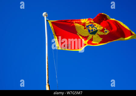 Montenegro, Beautiful montenegrin flag moving on flag pole in the wind with blue sky in summer - Stock Photo