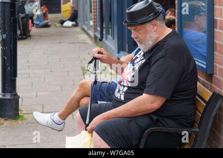Senior man with a grey beard sat on a seat wearing a black punk rock tee shirt and a plastic bowler hat,York,North Yorkshire,England. - Stock Photo