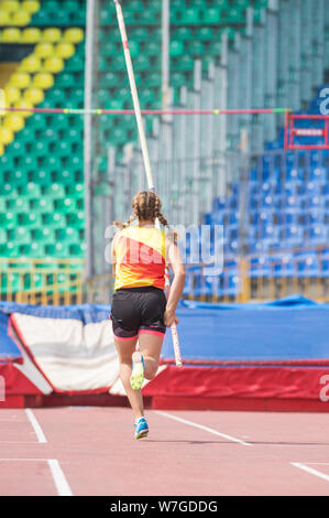 Pole vault - a young woman runs up holding a pole before jumping - Stock Photo
