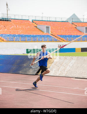Pole vault - a young man runs up holding a pole in stadium - Stock Photo