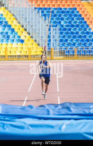 Pole vault - a bearded man runs up holding a pole before jumping. - Stock Photo