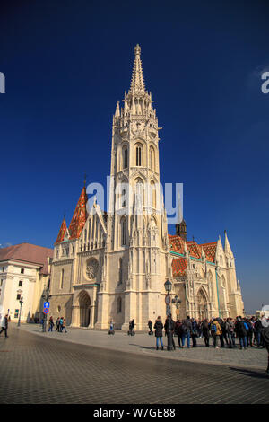 Budapest, Hungary, March 22 2018: Tourists visit the Matthias Church, part of the Buda Castle District on a sunny day on the Buda side of Budapest Hun - Stock Photo