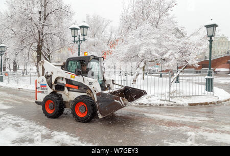 MOSCOW, RUSSIA - FEBRUARY 13,2019: Snow plow cleaning snow from city road. Snow clearing. Tractor clears the way after heavy snowfall. - Stock Photo