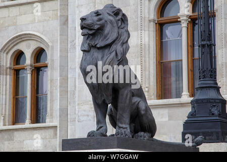 Budapest, Hungary - March 25, 2018: Black sculpture of lion as a guard on entrance to the building of Hungarian Parliament in Budapest, Hungary, view - Stock Photo
