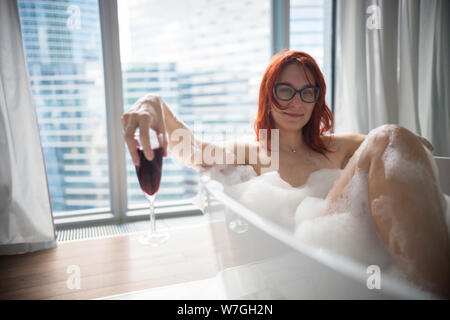 A ginger smiling woman lying in the foam bath and hold a glass of red wine - a view on a modern glass buildings from the panoramic windows