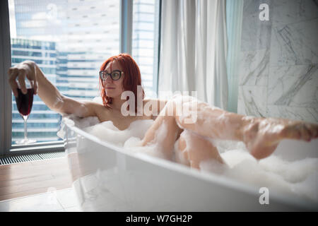 A ginger woman lying in the foam bath and looking to the side - holding a glass of red wine - a view on a modern glass buildings from the panoramic