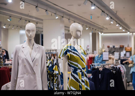 mannequins with modern clothes in fashion store display window. - Stock Photo