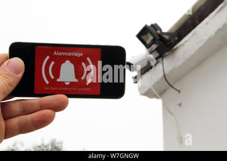 Mobile phone with a picture alarm system and the text 'Alarm' - Stock Photo