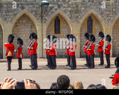 Tourists watch soldiers of the Household Troops during the changing the Castle Guard ceremony in Windsor Castle Lower Keep precincts, Windsor, UK - Stock Photo