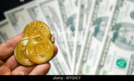 Bitcoins on the background of dollars. Golden Bitcoins. New virtual money. symbolic coins of bitcoin on banknotes of one hundred dollars. Exchange bit - Stock Photo