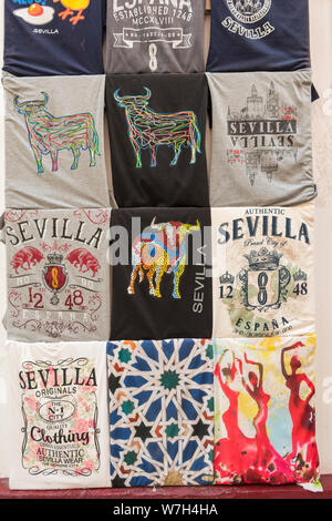 A display of T shirts with various images of Seville on them for sale as souvenirs in a tou=rist gift shop in Seville Spain. - Stock Photo