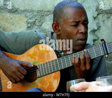 Cuban man plays and sings on his guitar - Stock Photo