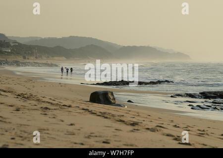 Durban, KwaZulu-Natal, South Africa, group of three people walking on Umhlanga Rocks beach, early morning, landscape, Africa, seascape - Stock Photo