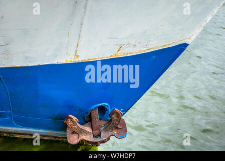 A rusty anchor on the side of a fishing ship in Helsinki - Stock Photo