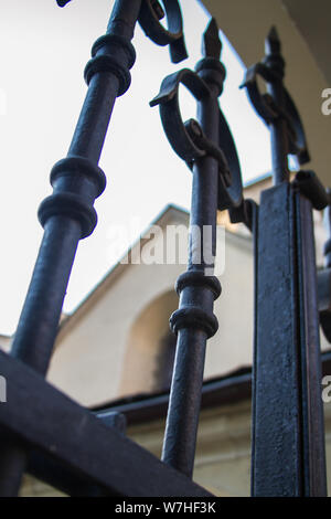 Bottom view of a spiers of a black metal fence around the church, selective focus - Stock Photo