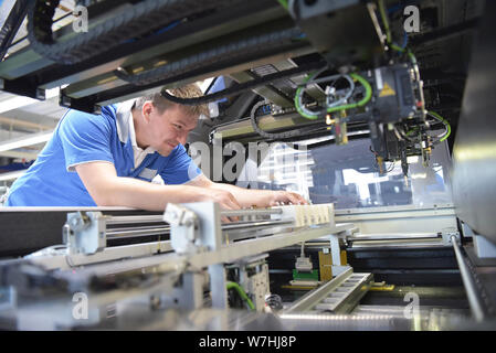engineer working on a machine for assembly and production of semiconductor boards in an industrial plant - Stock Photo