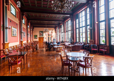 People playing cards in Saló llarg from Modernism Valencian building of Círculo Industrial de Alcoy, Alcoy, Alicante province, Spain - Stock Photo