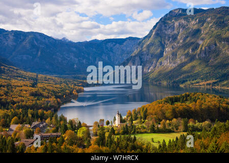 A ferry boat towards the town of Ribčev Laz next to Lake Bohinj and trees in autumn colors and Julian Alps mountains in a fall landscape in Slovenia. - Stock Photo