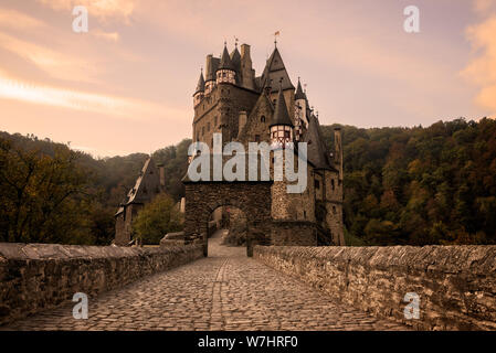 Cobblestone street with arch towards the medieval Burg Eltz Castle at sunrise near Mosel river in Wierschem, Rhineland-Palatinate, Germany. - Stock Photo