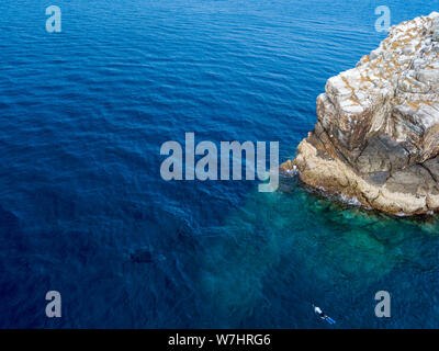 Aerial view of snorkelers looking at Manta Rays next to a large offshore rock in a tropical ocean (Black Rock, Myanmar) - Stock Photo