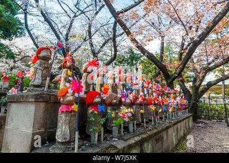 Jizo statues with red caps, protective deities for deceased children, Unborn Children Garden. Zojoji Temple, Buddhist Temple, Tokyo, Japan - Stock Photo