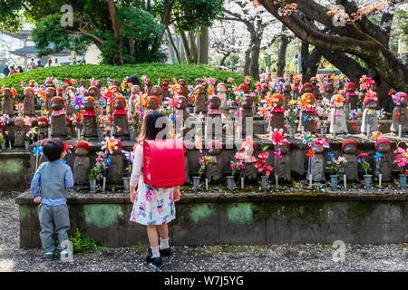 Two schoolchildren in front of Jizo statues with red caps, protective deities for deceased children, Unborn Children Garden. Zojoji Temple - Stock Photo