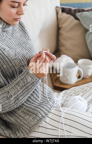 girl in a warm gray sweater knits sitting on a sofa in a cozy interior hygge