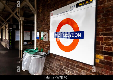 London overground tube style railway sign for West Croydon station.  White text on blue stripe, over red circle, on a white background, positioned against a brick wall.  Attached to the wall are separate recycle bins for both plastic and paper. - Stock Photo
