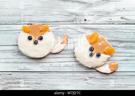 Fun food for kids. Rice cakes in the shape of foxes lying on a rustic white table. Fox is made from cream cheese, peanut butter, apple slices, oranges - Stock Photo
