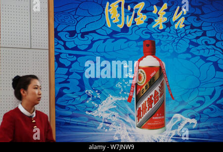 --FILE--A Chinese employee walks past an advertisement for Kweichow Moutai during an exhibition in Tianjin, China, 28 October 2012.   Kweichow Moutai, - Stock Photo