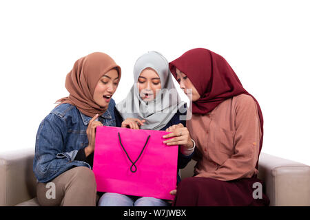 Young hijab women surprised open their shopping bag - Stock Photo