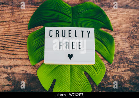 cruelty free message on lightbox with leaf and wood texture background, concept of vegan products and ethics - Stock Photo