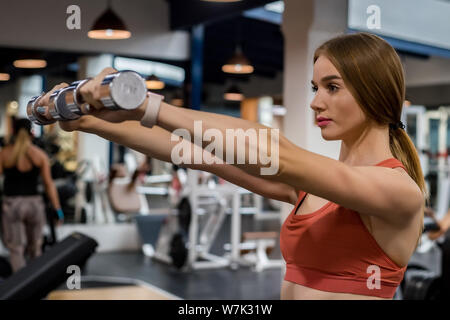Beautiful young woman trains deltoid in gym - Stock Photo