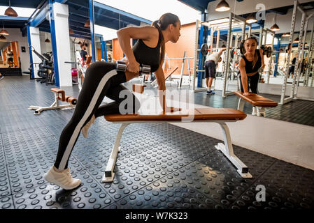 Back view young woman trains deltoid in front of gym mirror - Stock Photo