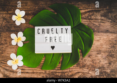cruelty free message on lightbox with tropical settings on banana leaf and with plumeria flowers, concept of vegan products and ethics - Stock Photo