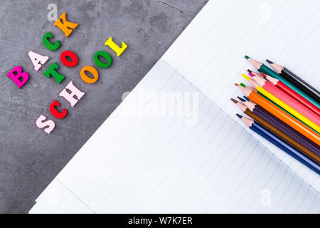 The layout of school supplies on a dark gray background. The view from the top. Back to school. Flat lay - Stock Photo