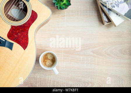 Top view of cosy home scene. Guitar, books, cup of coffee and succulent plants over wooden background. Copy space. - Stock Photo