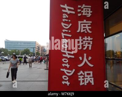 --FILE--Pedestrians walk past a signboard of Hai Di Lao Hotpot in Beijing, China, 28 May 2016.   Beijing's food safety watchdog has begun a two-week s - Stock Photo