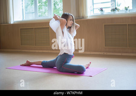 Young acrobatic woman with blonde hair sitting on the yoga mat and doing stretching exercises - Stock Photo