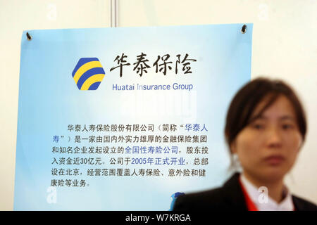 --FILE--A Chinese employee walks past an introduction of Huatai Insurance Group during an exhibition in Shanghai, China, 23 November 2013.   China's H - Stock Photo