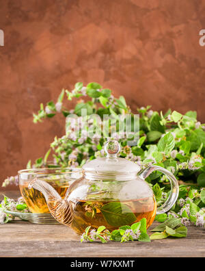Fresh aromatic tea with melissa mint leaves glass teapot on a rustic background. Healing herbal drink. Vertical frame. - Stock Photo