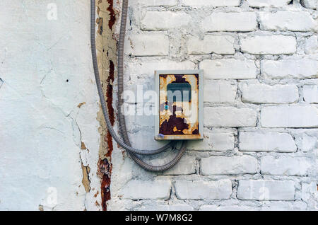 Rusty Distribution Board Metal Box with Electricity Meter, Seal and Two Cables in Steel Coil Housing on a White Brick Wall Outdoors. - Stock Photo