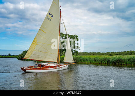 A lone sailor on a traditional sailing boat tacking along the River Bure in the Norfolk Broads - Stock Photo